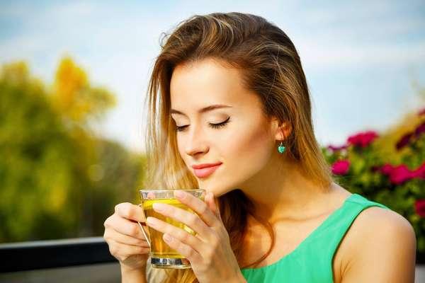 Деушка пьет чай с имбирем и лимоном для похудения